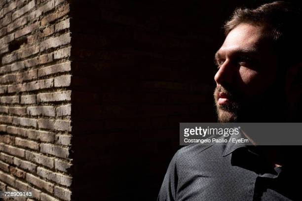 thoughtful man standing against wall on sunny day - costangelo pacilio foto e immagini stock