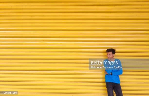 Thoughtful Man Standing Against Yellow Corrugated Iron