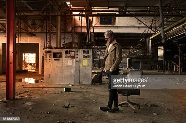 Thoughtful Man Standing By Chair In Abandoned Warehouse