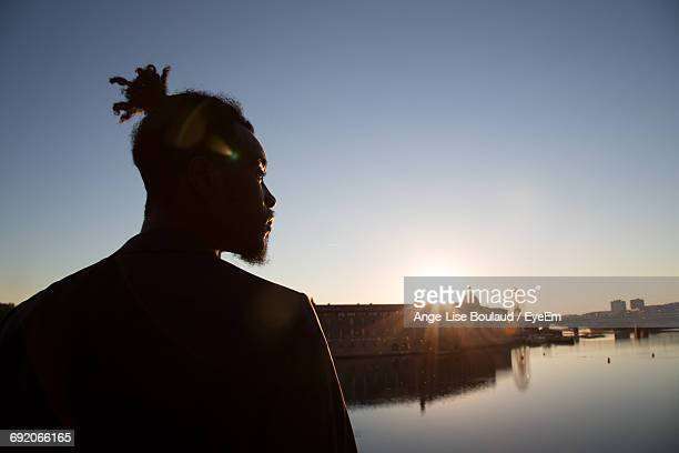 Thoughtful Man Standing By Lake And City Against Clear Sky During Sunset