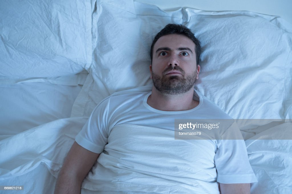 Thoughtful man trying to sleep in his bed at night : Stock Photo