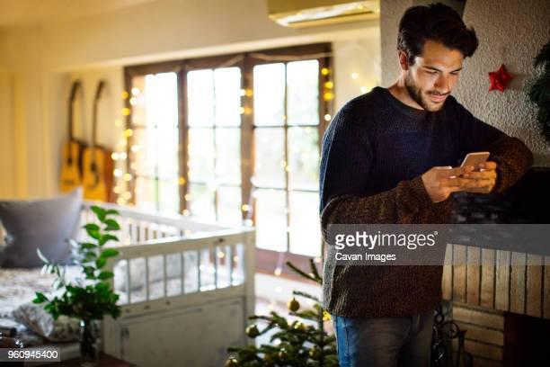 Thoughtful man using smart phone while standing at home during Christmas