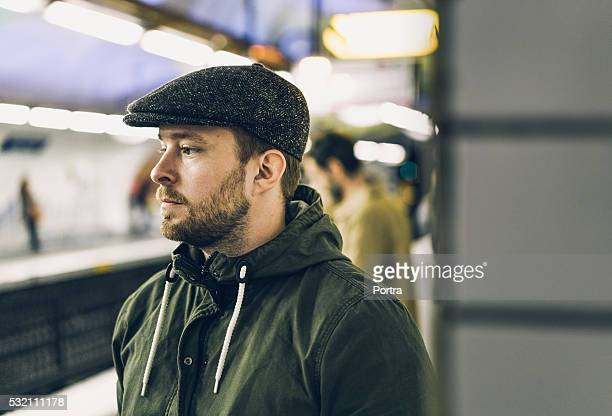 thoughtful man wearing cap at railroad station - flat cap stock pictures, royalty-free photos & images