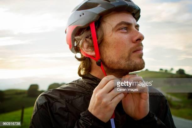 thoughtful man wearing helmet against sky - サイクリングヘルメット ストックフォトと画像