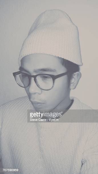 Thoughtful Man Wearing Knit Hat And Eyeglasses Looking Down
