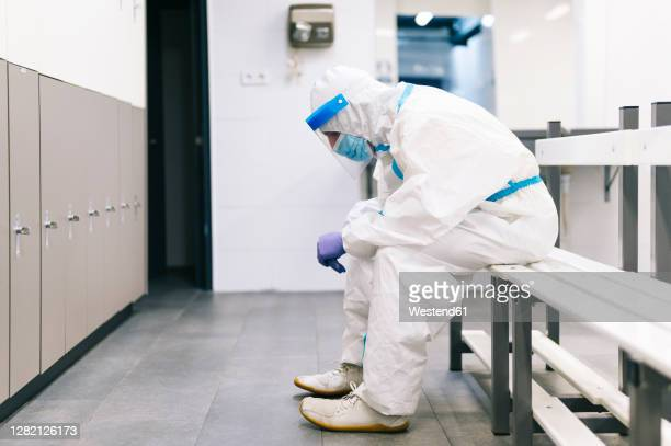 thoughtful man wearing protective suit sitting on bench in hospital - intensive care unit stock pictures, royalty-free photos & images