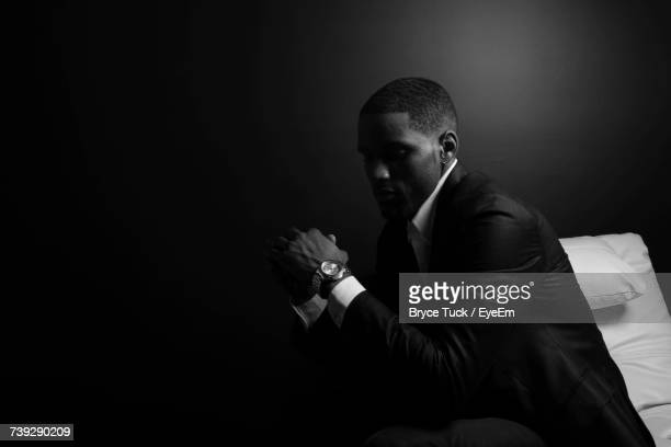 Thoughtful Man Wearing Suit Sitting On Bed Against Wall