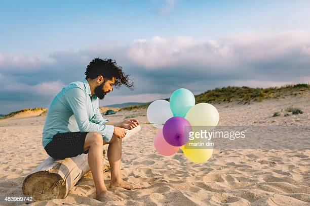 Thoughtful man with balloons at the beach