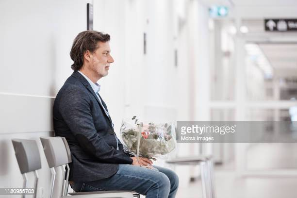 thoughtful man with bouquet waiting in corridor - regione dell'oresund foto e immagini stock