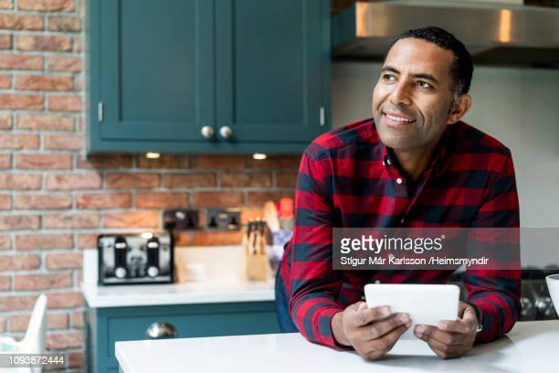 thoughtful man with digital tablet in kitchen - 45 49 years stock pictures, royalty-free photos & images
