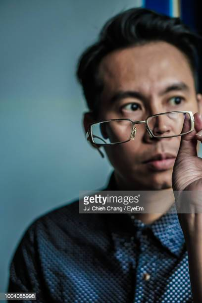 Thoughtful Man With Eyeglasses Sitting At Home