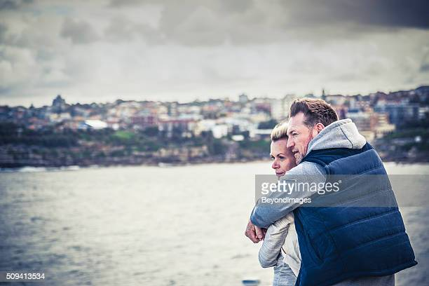 Thoughtful mature adult couple embracing and looking out to sea