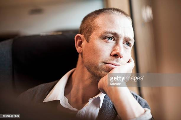 Thoughtful mature businessman sitting in train