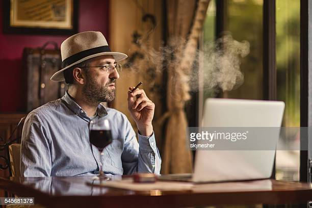 Thoughtful mature businessman smoking a cigarette.