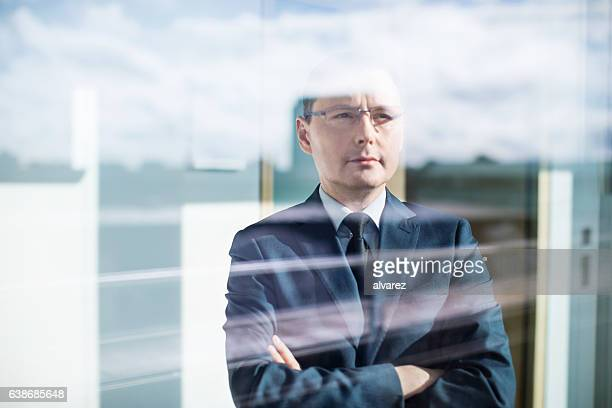 Thoughtful mature businessman standing behind glass