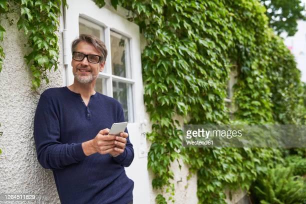 thoughtful mature man holding smart phone while leaning on wall at yard - manga longa - fotografias e filmes do acervo