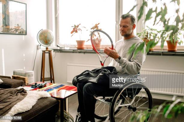 Thoughtful mature man holding tennis racket while sitting on wheelchair at home
