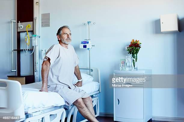 thoughtful mature man in hospital ward - bett stock-fotos und bilder
