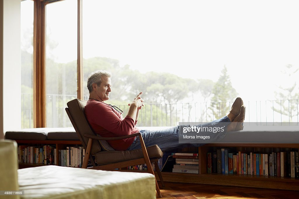 Thoughtful mature man relaxing on armchair : ストックフォト