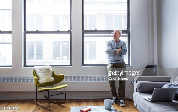 thoughtful mature man standing arms crossed while leaning on window at home - ein mann allein stock-fotos und bilder