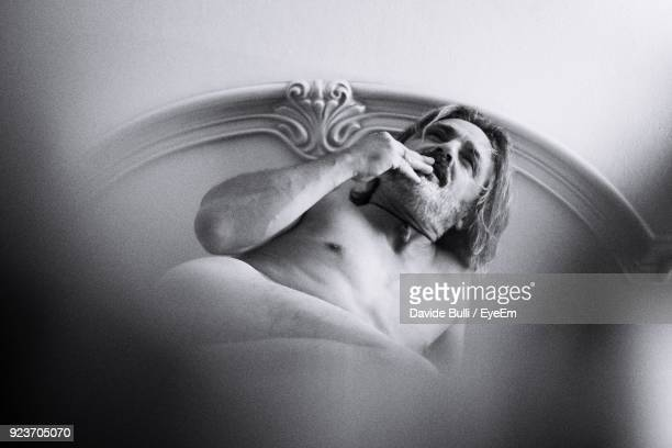 Thoughtful Mature Shirtless Man On Bed At Home