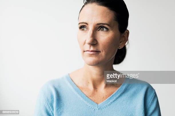 Thoughtful mature woman against white background