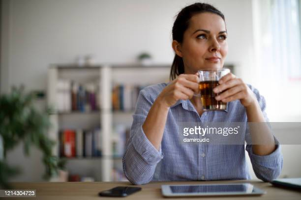 thoughtful mature woman drinking tea at home - tea hot drink stock pictures, royalty-free photos & images
