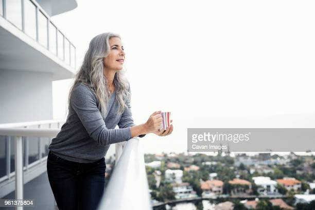 thoughtful mature woman holding coffee mug while standing on balcony - aventura florida stock photos and pictures
