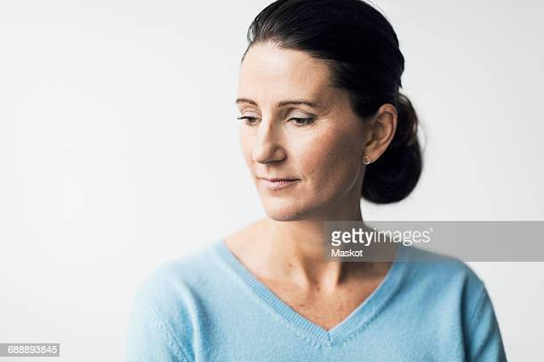Thoughtful mature woman looking down against white background