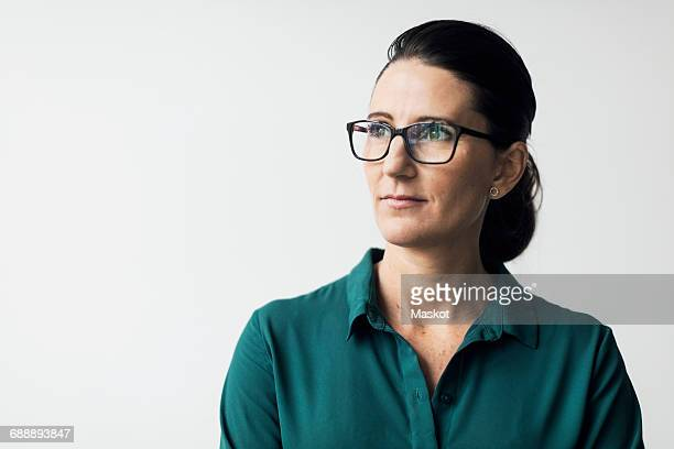 thoughtful mature woman wearing eyeglasses against white background - wegkijken stockfoto's en -beelden