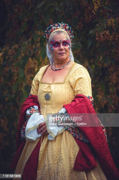 thoughtful mature woman wearing period costume while standing against tree - steve guessoum stockfoto's en -beelden