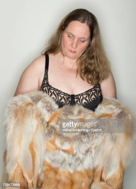 Thoughtful Mature Woman With Fur Coat Standing Against Gray Background