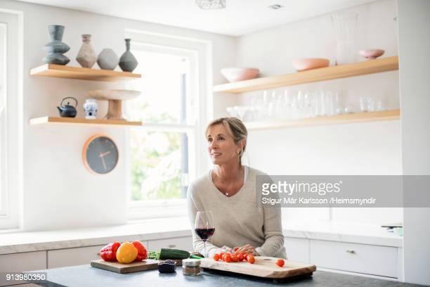 donne mature premurose sedute sull'isola della cucina - articoli casalinghi foto e immagini stock