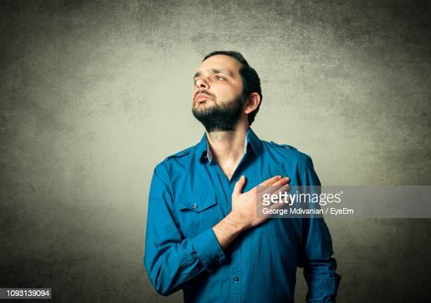 thoughtful mid adult man standing with hand on chest against black background - 宣誓 ストックフォトと画像