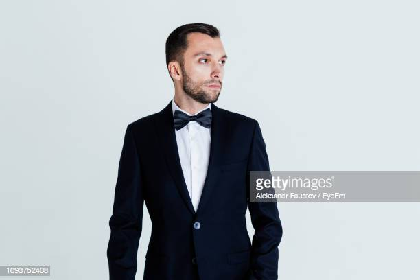 thoughtful mid adult man wearing tuxedo against blue background - bow tie stock pictures, royalty-free photos & images