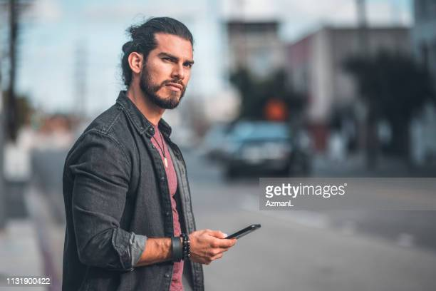thoughtful mid adult man with smart phone in city - man bun stock pictures, royalty-free photos & images