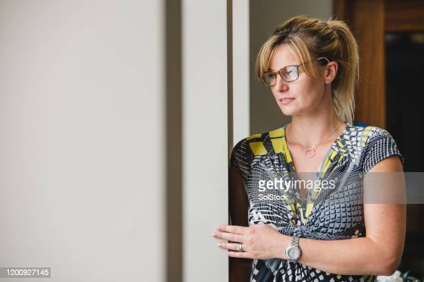 thoughtful mid adult woman in doorway - hair back stock pictures, royalty-free photos & images