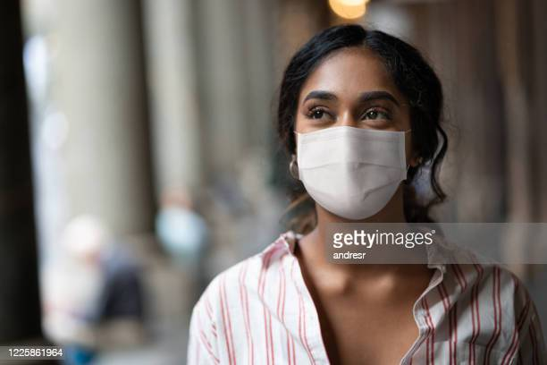 thoughtful mixed-race woman on the street wearing a facemask - indian ethnicity stock pictures, royalty-free photos & images