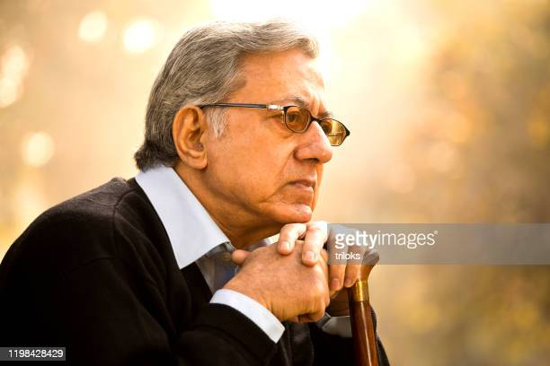 thoughtful old man sitting on park bench - ethnicity stock pictures, royalty-free photos & images