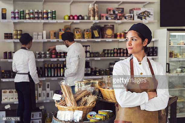 Thoughtful owner standing arms crossed while colleagues working in grocery store