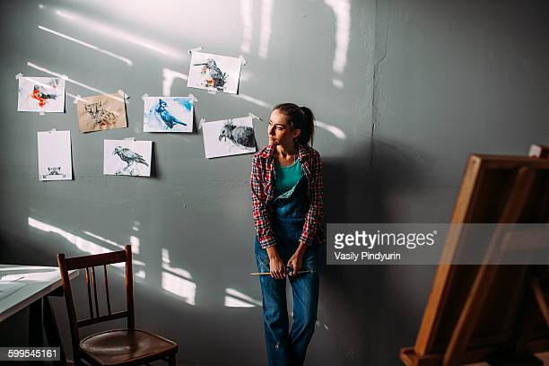 thoughtful painter leaning on wall in art studio - art studio stock pictures, royalty-free photos & images