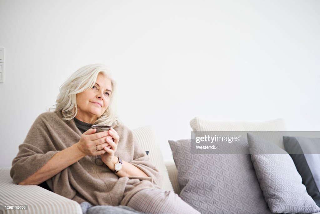 Thoughtful retired woman holding coffee cup while sitting on sofa against white wall at apartment : Stockfoto