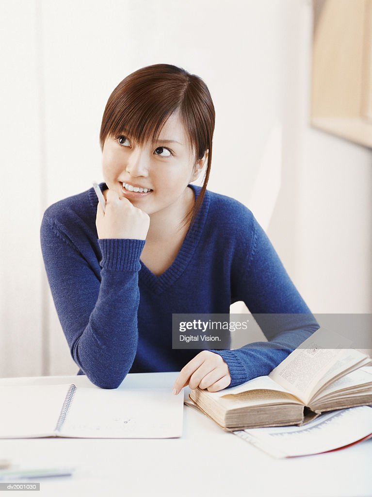 Thoughtful Schoolgirl Sitting at a Desk With Her Hand on Her Chin With Her Homework : Stock Photo