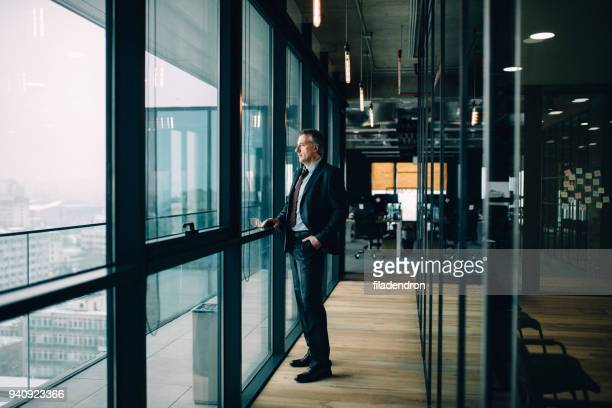 thoughtful senior businessman - looking through window stock pictures, royalty-free photos & images