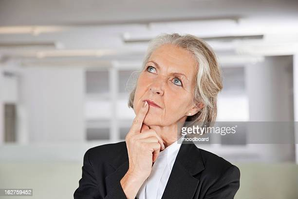 thoughtful senior businesswoman looking up in office - one senior woman only stock pictures, royalty-free photos & images