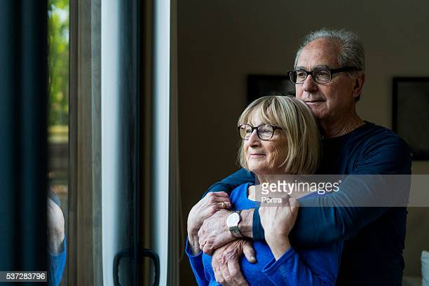thoughtful senior couple looking through window - contemplation couple stock pictures, royalty-free photos & images