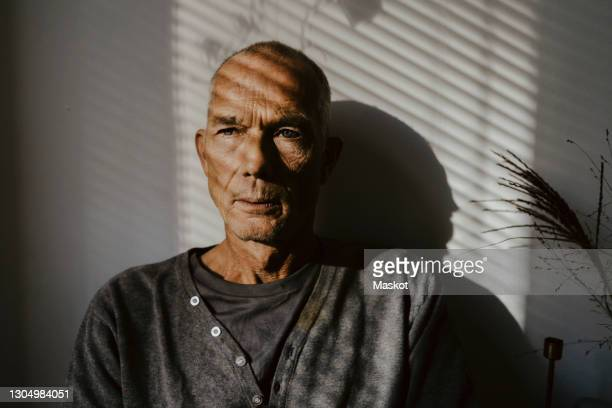 thoughtful senior man against wall at home - distant stock pictures, royalty-free photos & images