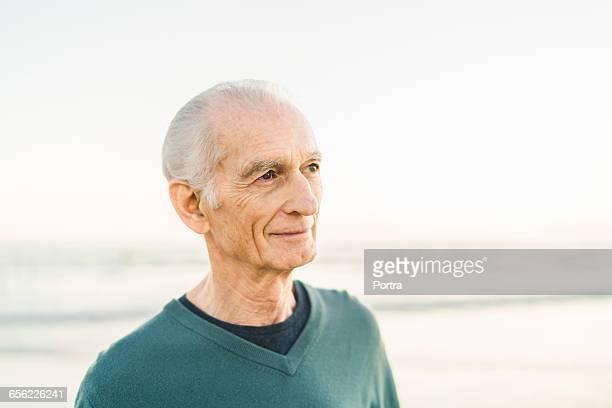 Thoughtful senior man at beach against clear sky