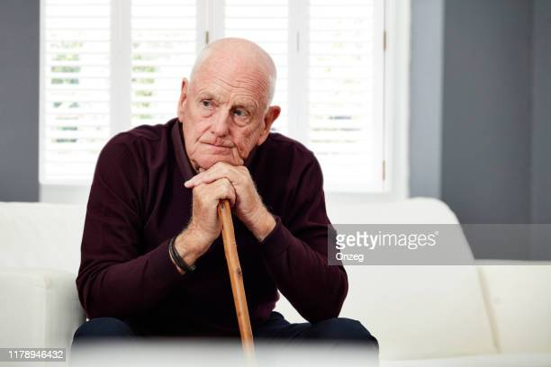 thoughtful senior man at home - one senior man only stock pictures, royalty-free photos & images