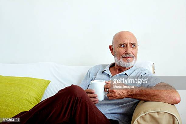 thoughtful senior man holding coffee mug on sofa - hair loss stock pictures, royalty-free photos & images